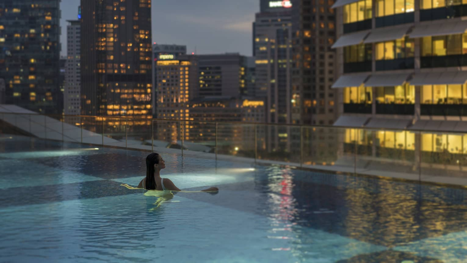 A woman swims in an infinity pool with a view of the city skyline