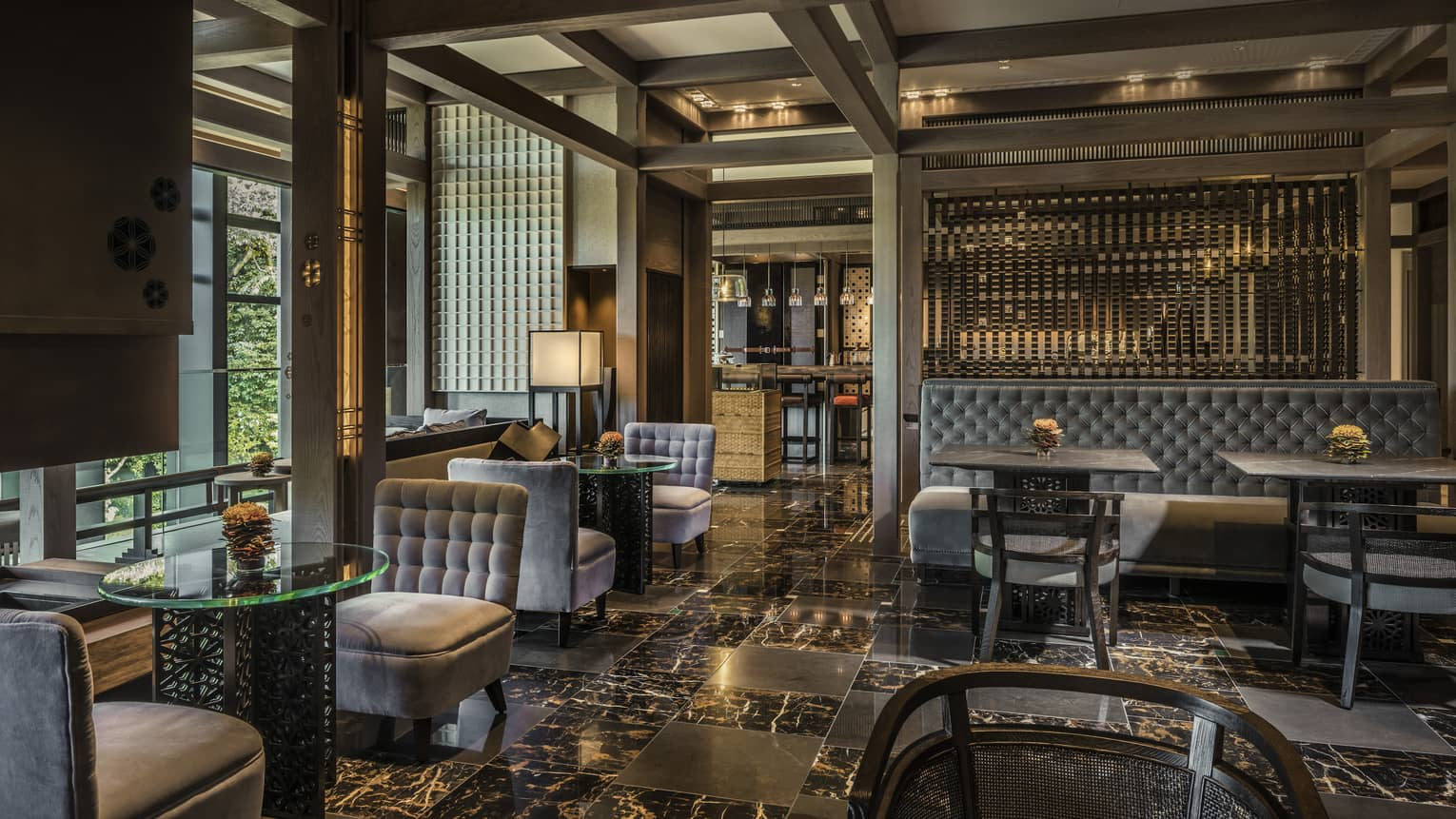 Plush grey velvet sofas, chairs on black marble floors in The Lounge dining room