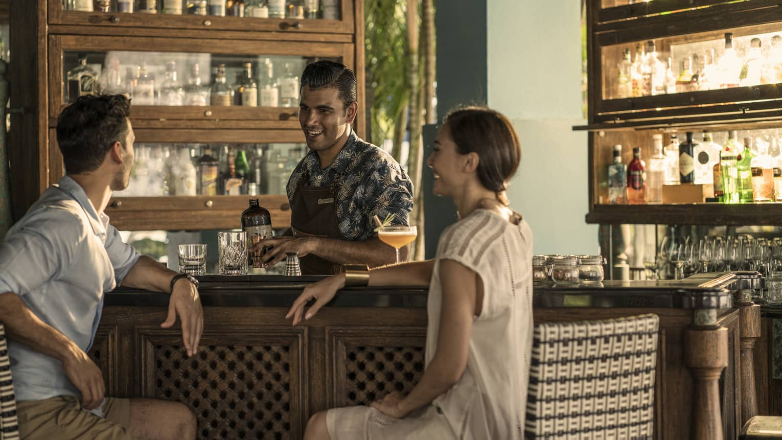 Two guests chat with a bartender at rhu bar while he makes a drink