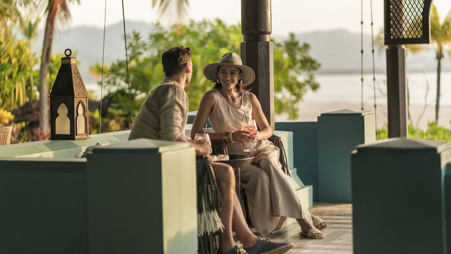 A man and woman are sitting in an outdoor Rhu Bar area overlooking the ocean holding cocktails