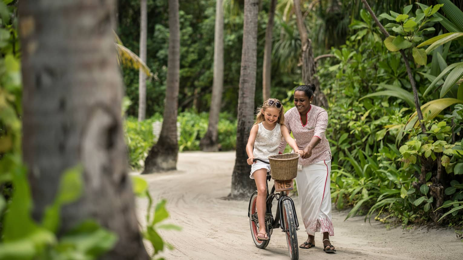 Hotel staff helps young girl ride bicycle with woven basket on tropical resort path
