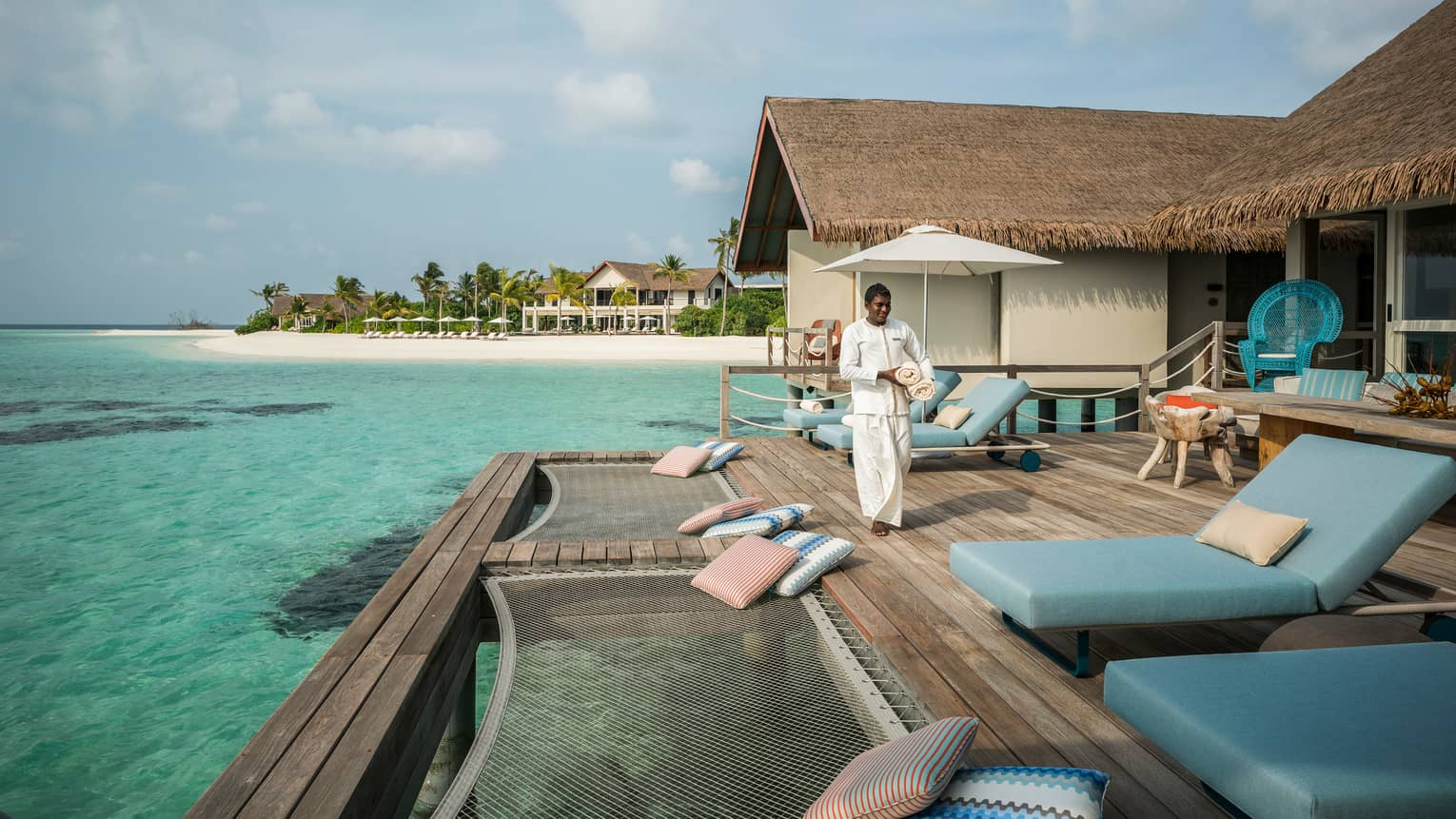 Hotel staff carries towels across Water Villa patio to blue lounge chairs, hammocks over lagoon