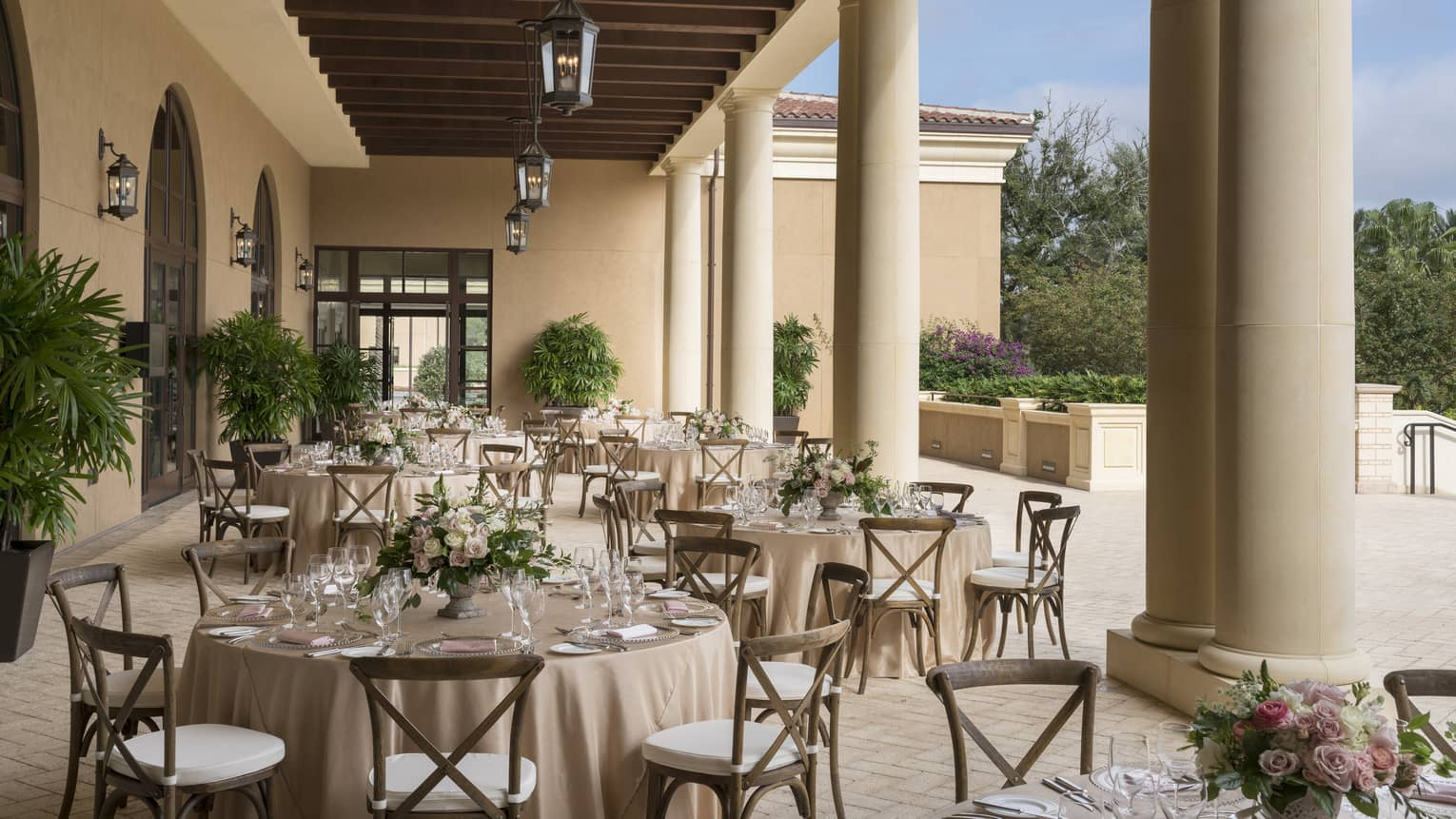 The Grand Ballroom Terrace is ready for guests with circular tables set with a cream table cloth, clear glass plates and tableware and a green floral arrangement in the center