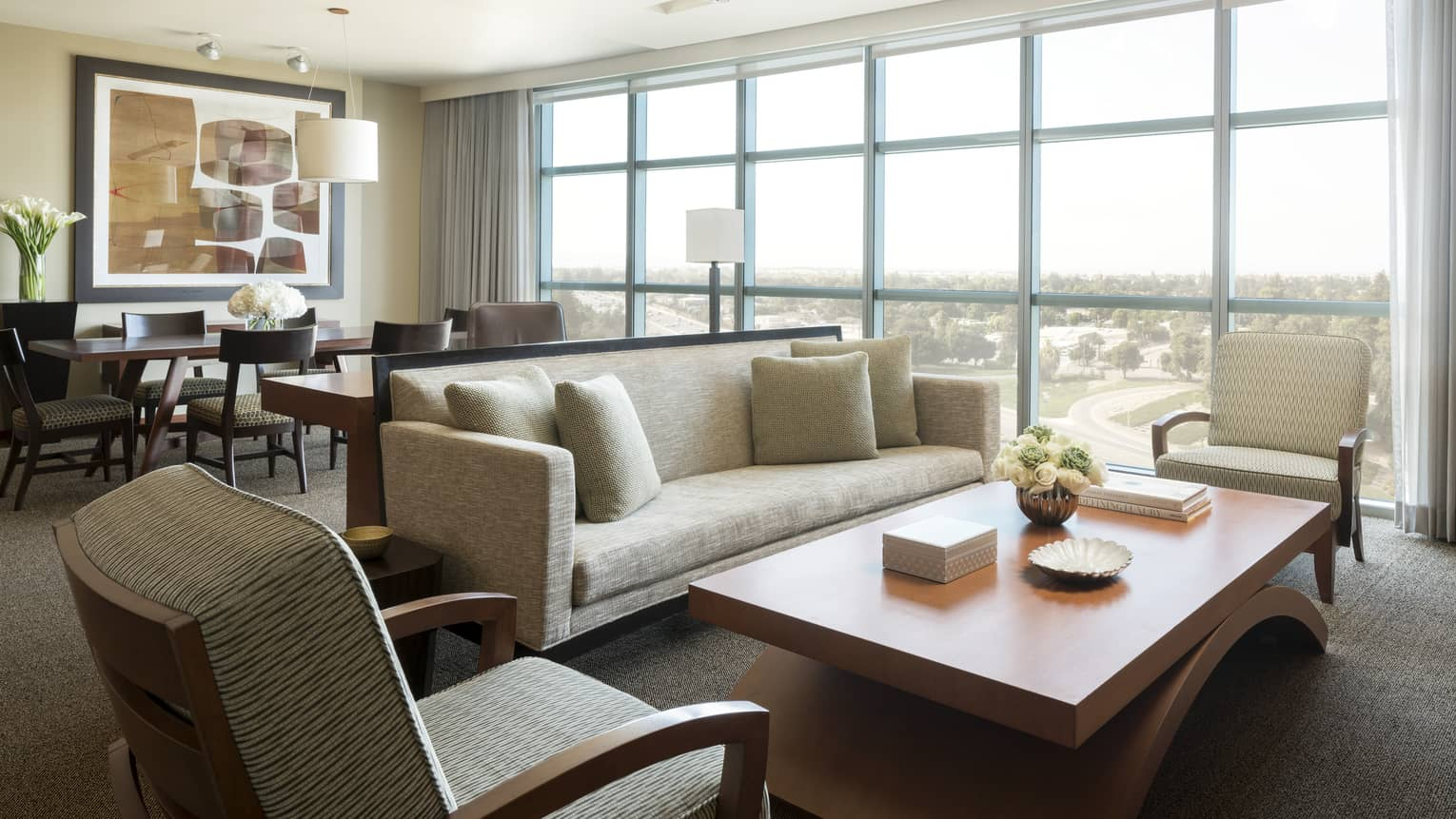 Luxury Suite bright seating area, dining table by floor-to-ceiling windows