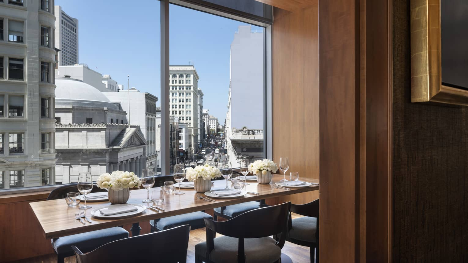 Private dining table with fresh white flowers by sunny window with San Francisco city view