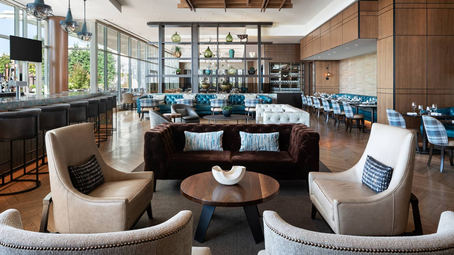 The interior of cinderhouse restaurant at four seasons saint louis is decorated with a navy accent wall, light wooden floor with a chevron style, black tables and camel colored leather chairs