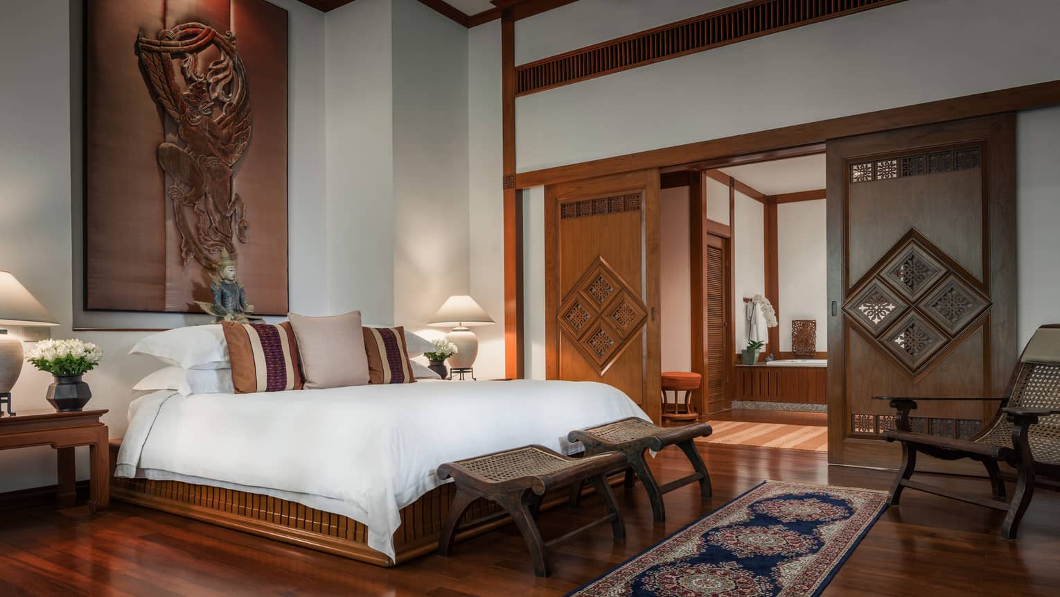 Penthouse Residence bedroom with high ceilings, wood sculpture over bed, sliding wood doors