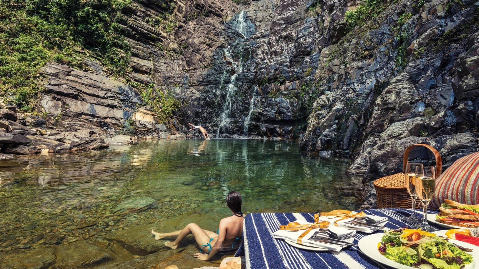 Woman wades in water at bottom of waterfall by picnic lunch set up on rocks