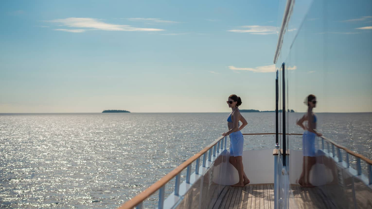 Woman wearing swimsuit stands at yacht balcony, looks out over water