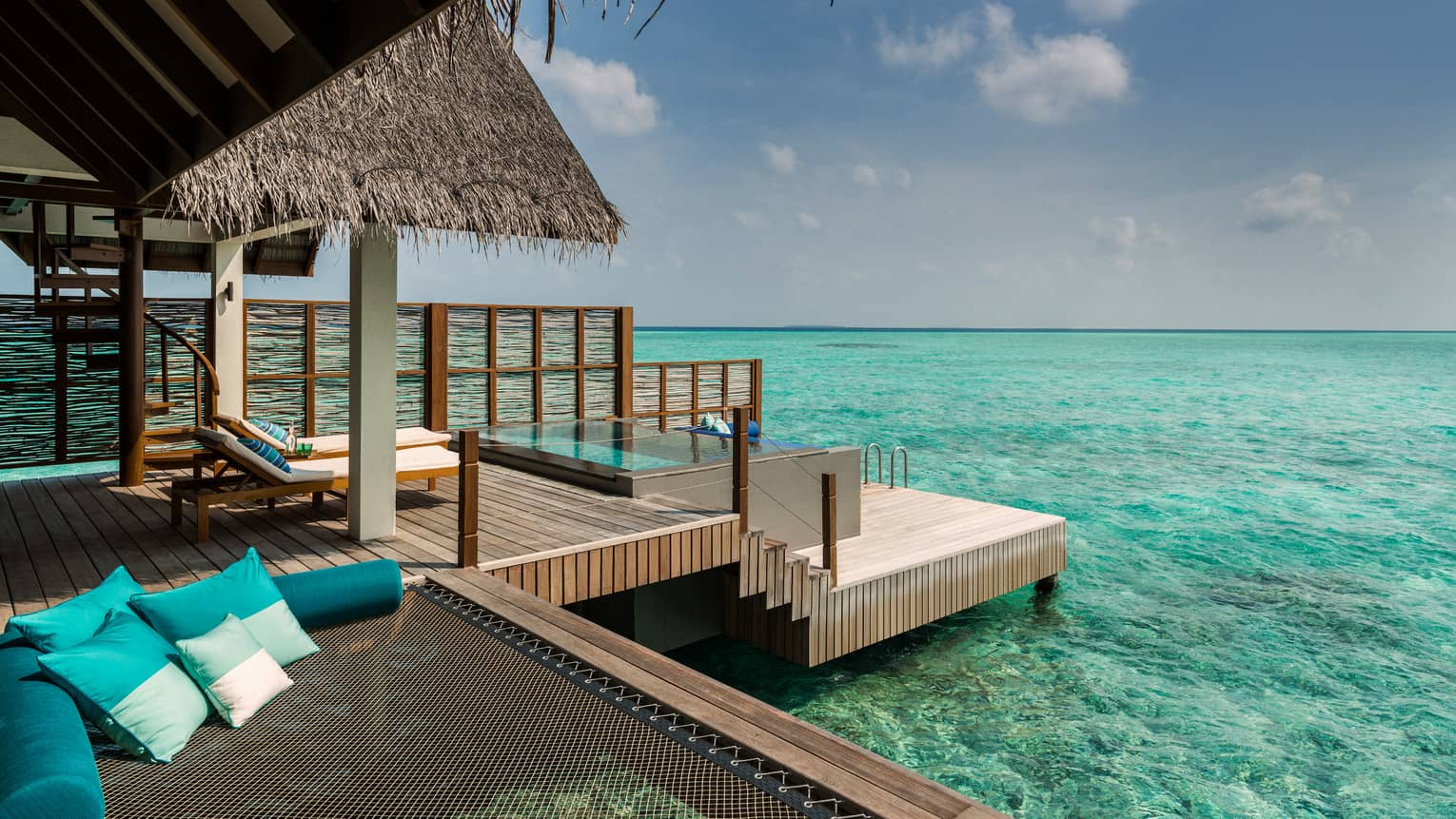 Tiered deck, lounge chairs under thatched roof on overwater villa