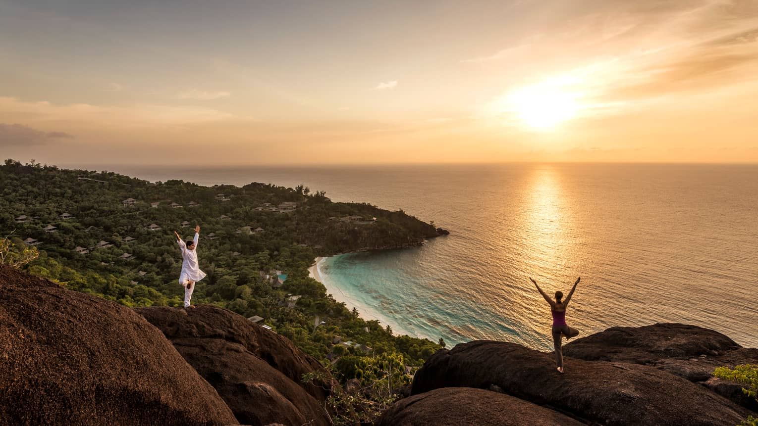 Woman and man stand apart on large boulders overlooking canopy of trees, ocean at sunrise