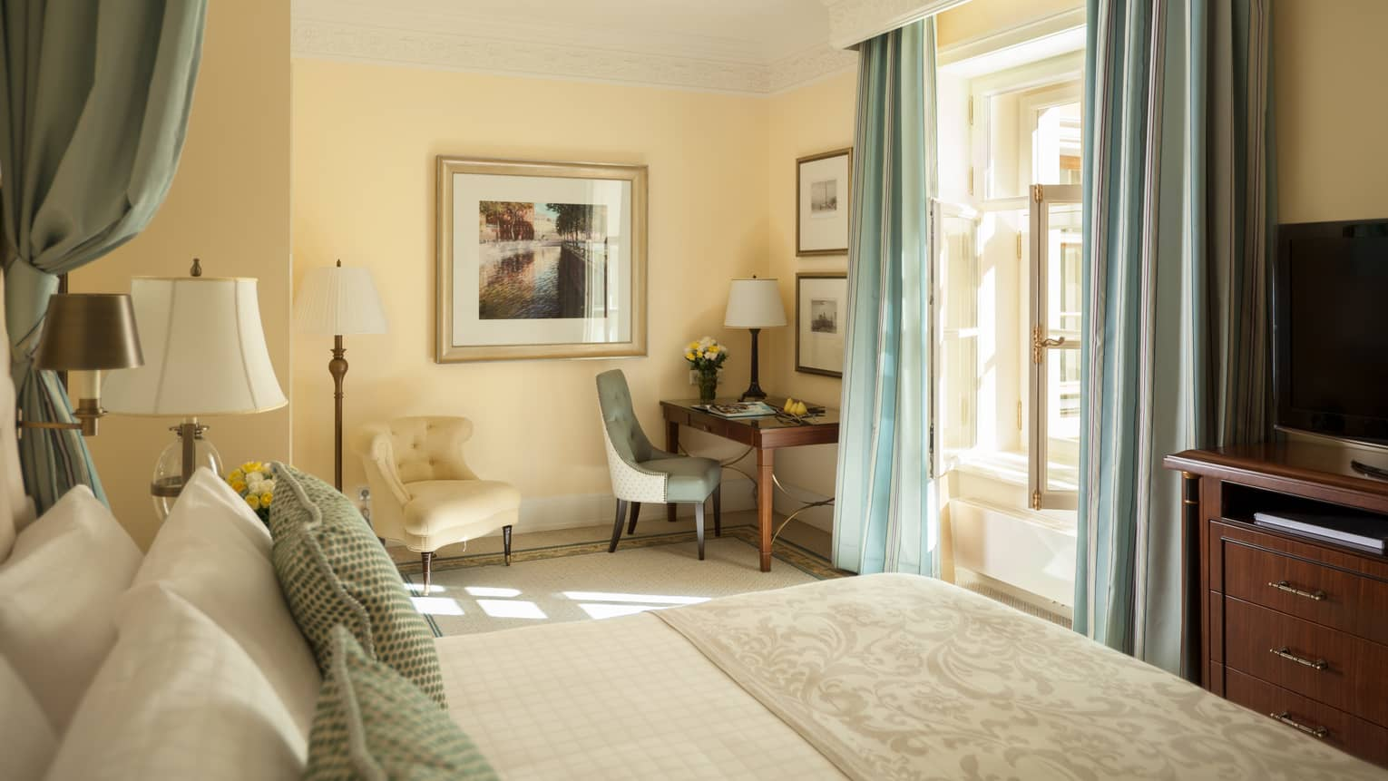 Deluxe Room bed in front of sunny picture window with pale blue curtains, white chair, desk