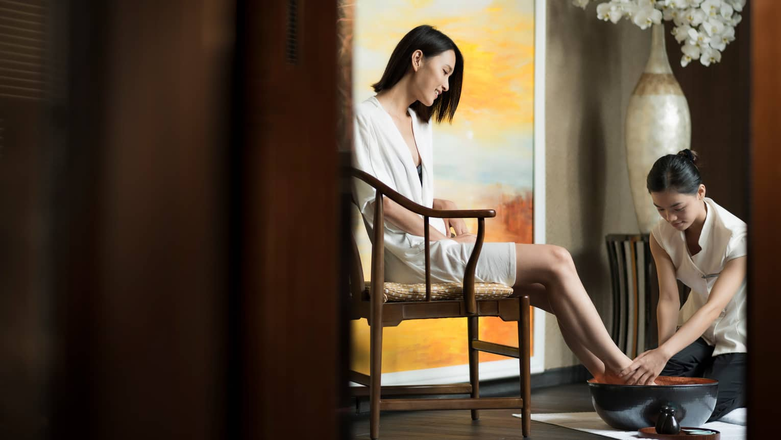 Spa staff rinses woman's feet in bowl as she sits in chair in white robe