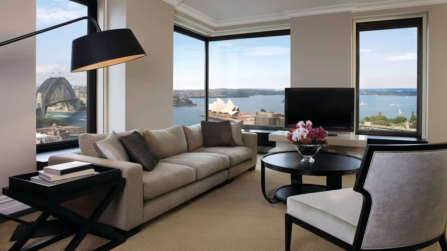 Presidential Suite reading lamp over long plush sofa, armchairs, table by sunny corner windows