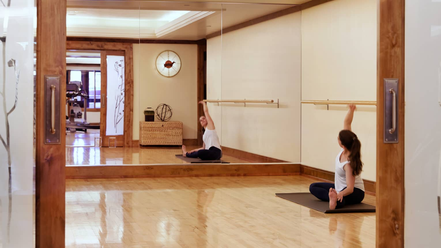 A woman stretches on a yoga mat within a workout studio with a mirrored wall