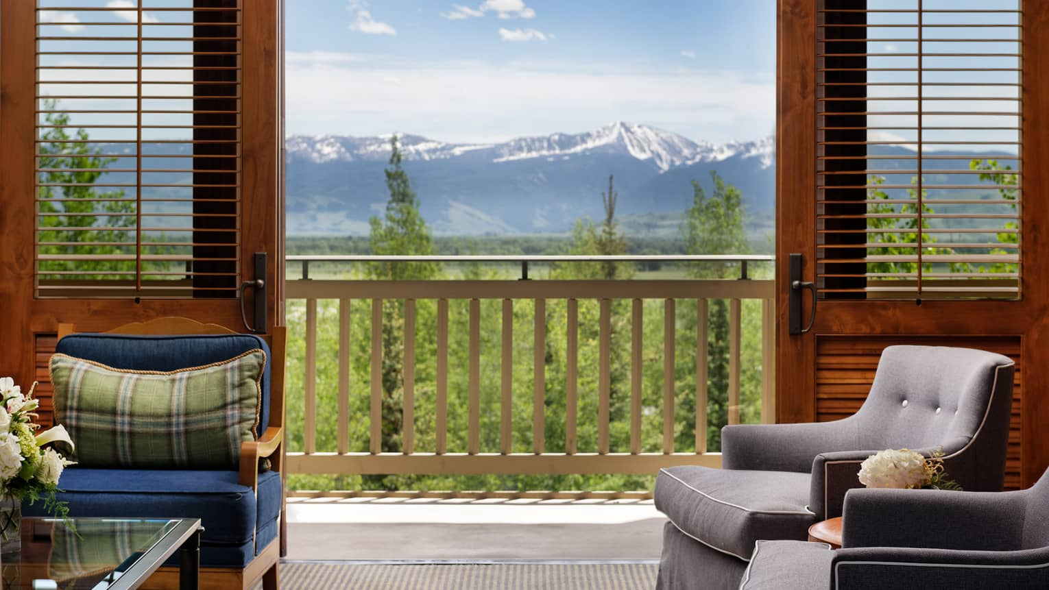 View from the seating area of Residence 852, with open doors to a patio and snow-capped mountains in the distance