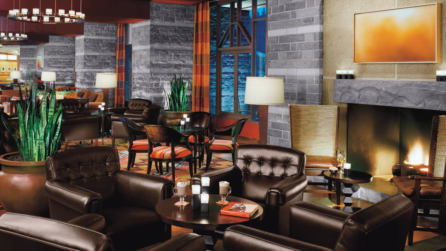 Sidecut lounge large black leather armchairs around cocktail tables, by slate fireplace