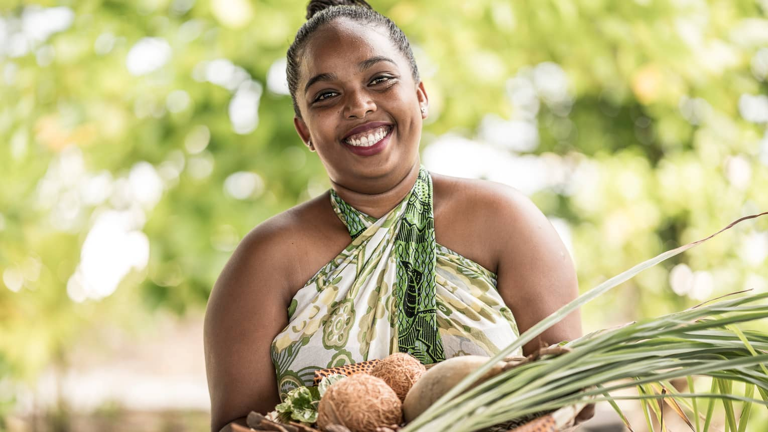 Smiling woman holds spa basket with coconuts, lemongrass, herbs