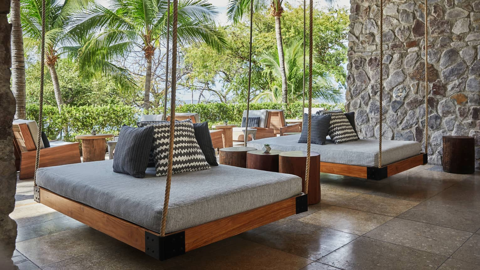 Two hanging patio beds held by ropes with thick grey cushions, accent pillows