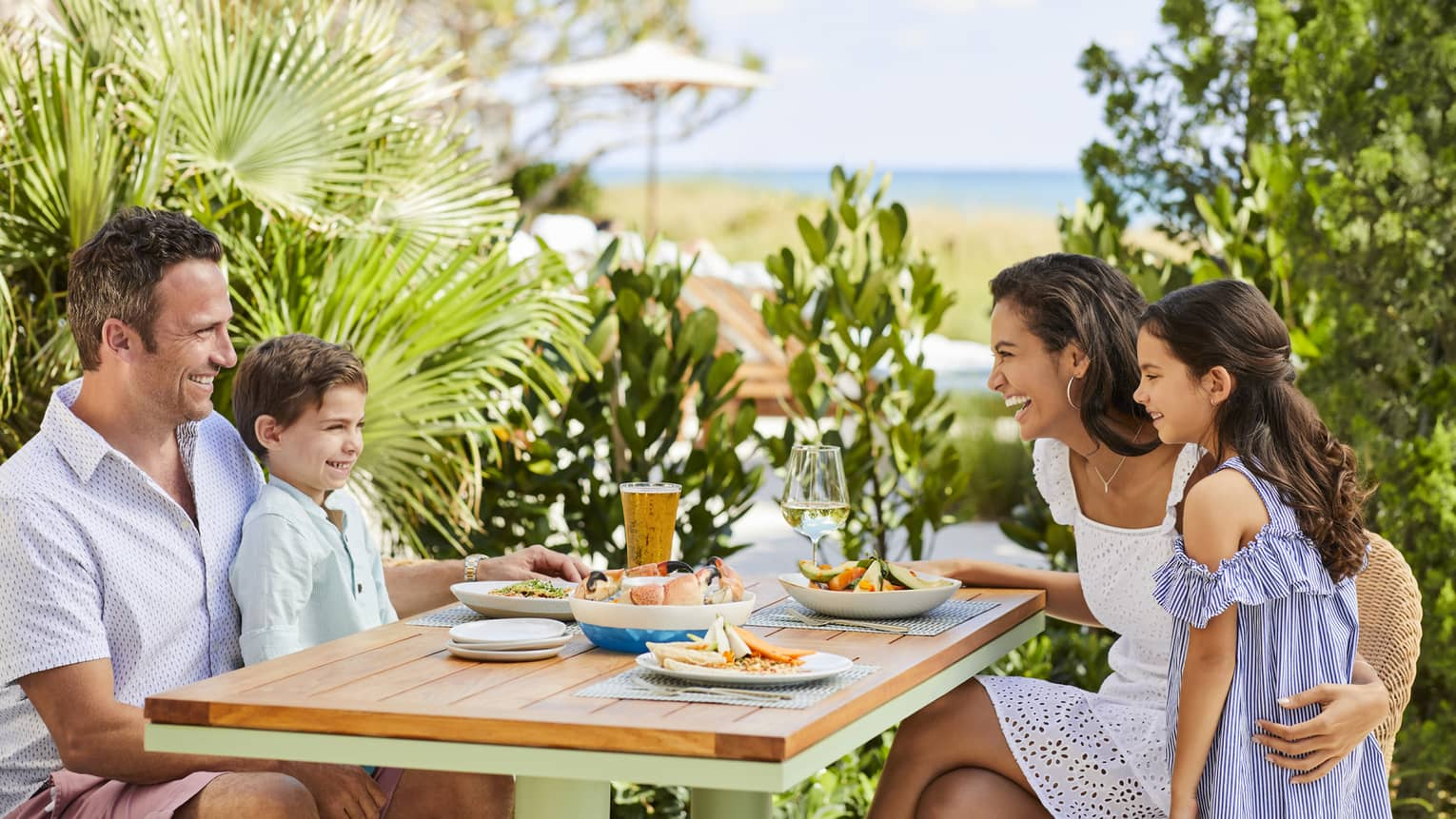 A family enjoys seafood and salad at a secluded outdoor table