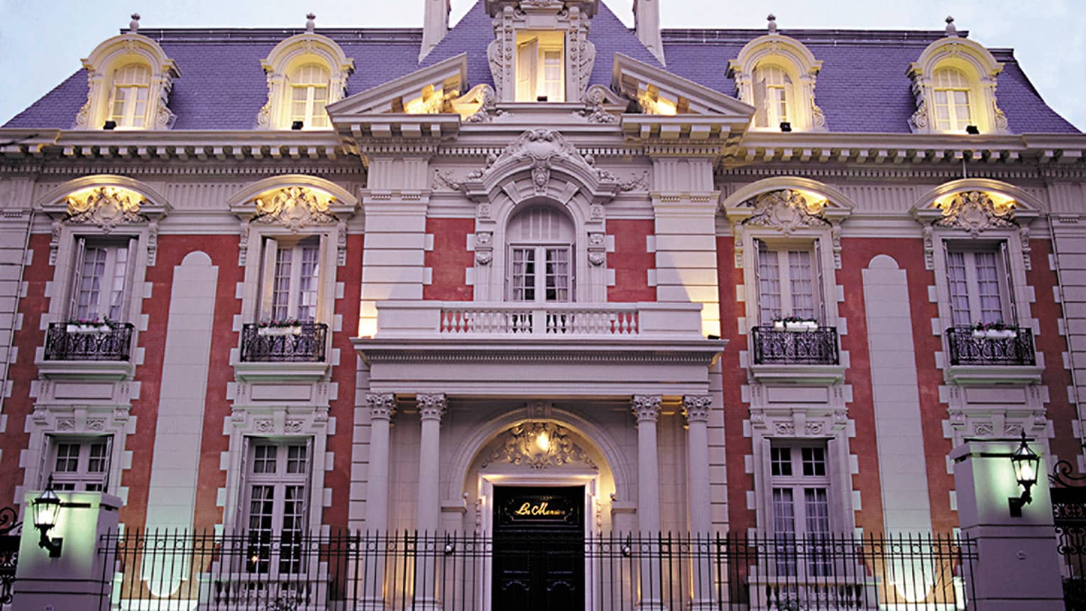 Four Seasons Buenos Aires hotel La Mansión historic exterior with lights at dusk, black fence in front