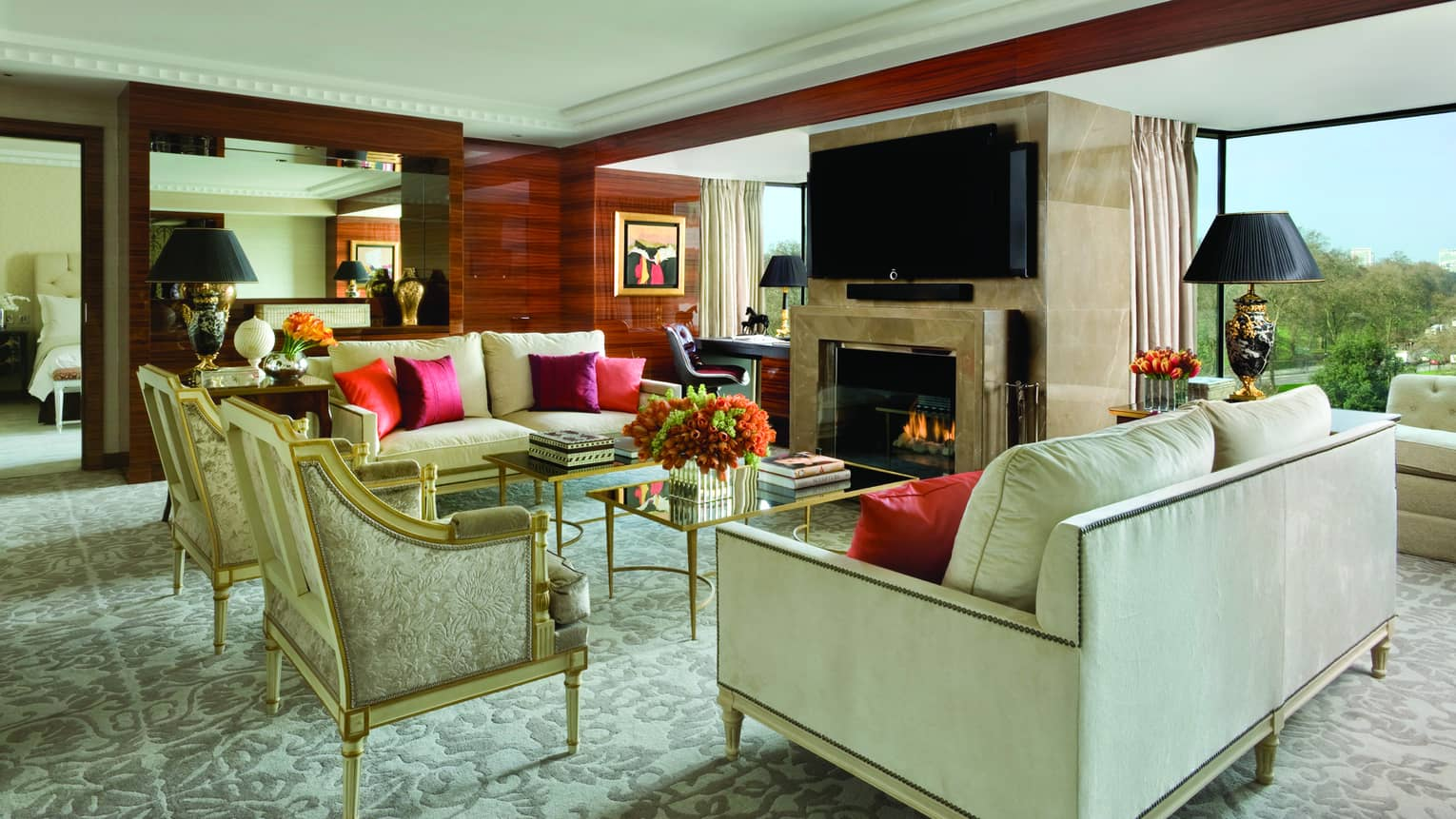 Presidential Suite elegant white sofas, armchairs by marble fireplace, desk, windows