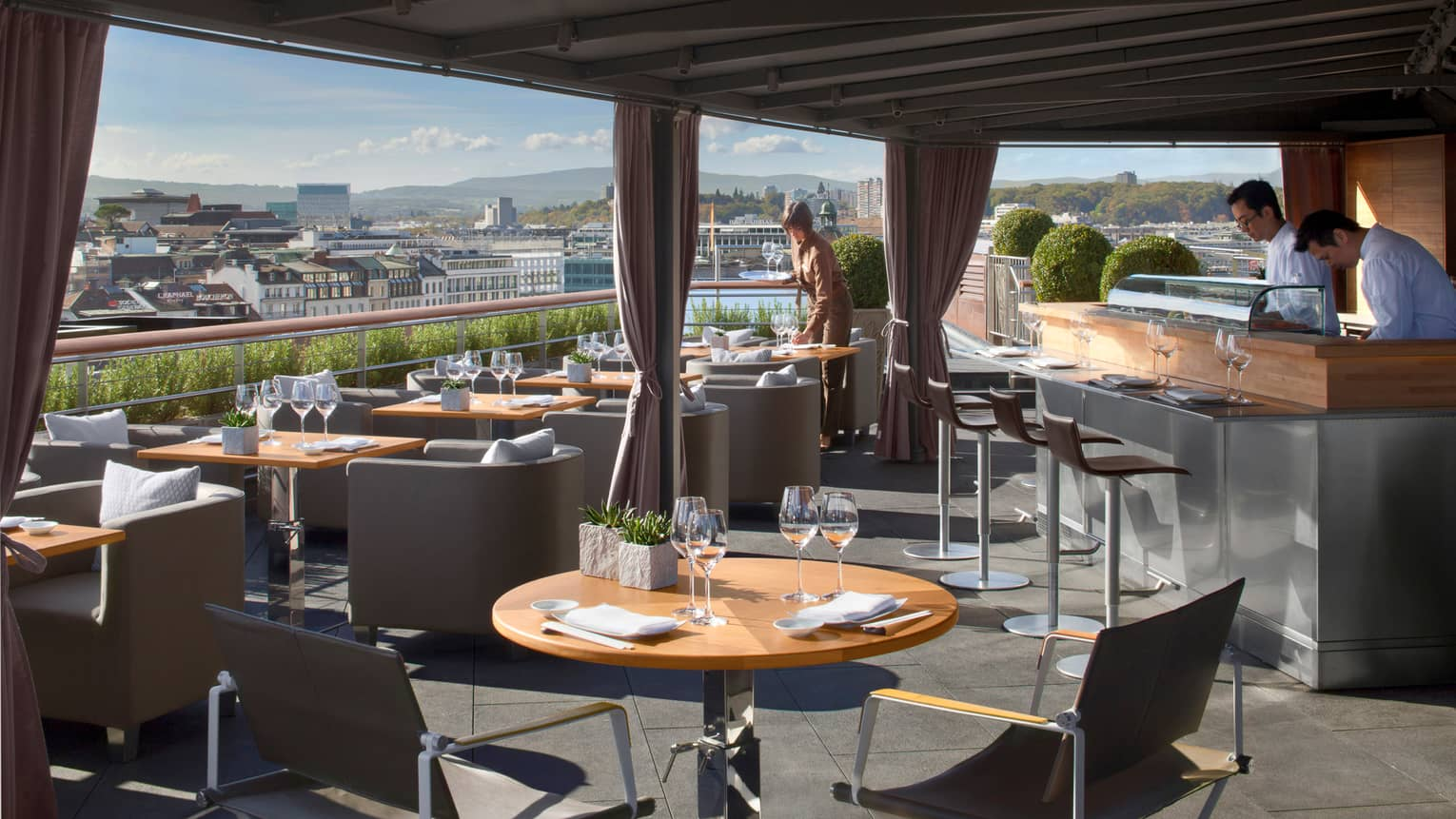 Feast on 360˚ rooftop patio dining tables and chairs under awning on sunny day, bartenders and server sets table