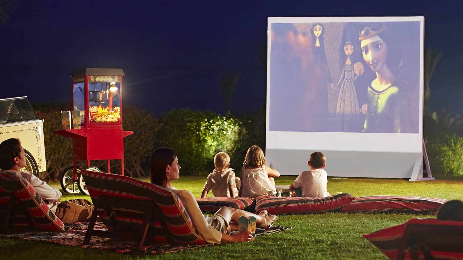 Children, parents lounge on pillows on grass in front of large outdoor movie screen at night