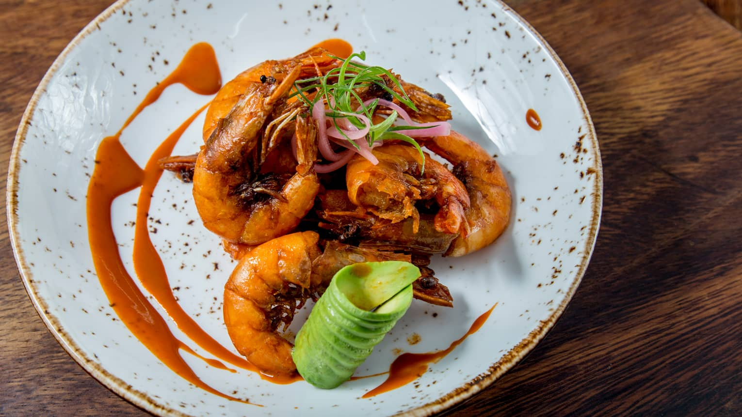 Fried seafood in sauce on plate with avocado spiral