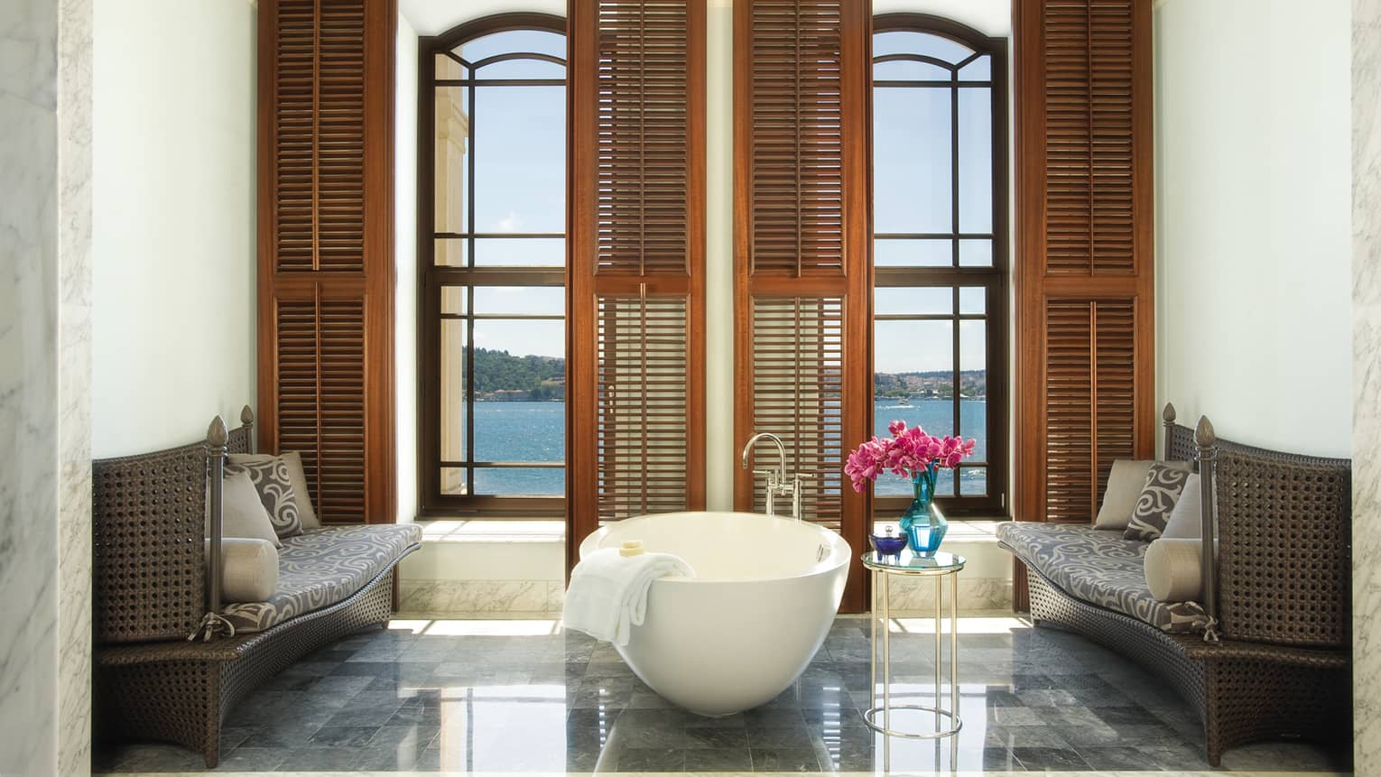 White freestanding tub in front of tall windows, wood shutters in marble bathroom