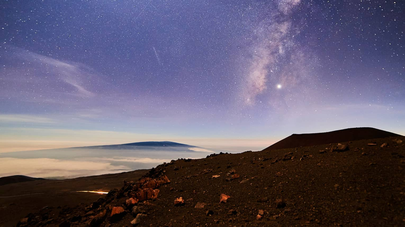 Sunrise under starry sky above mountain, volcanic rocks