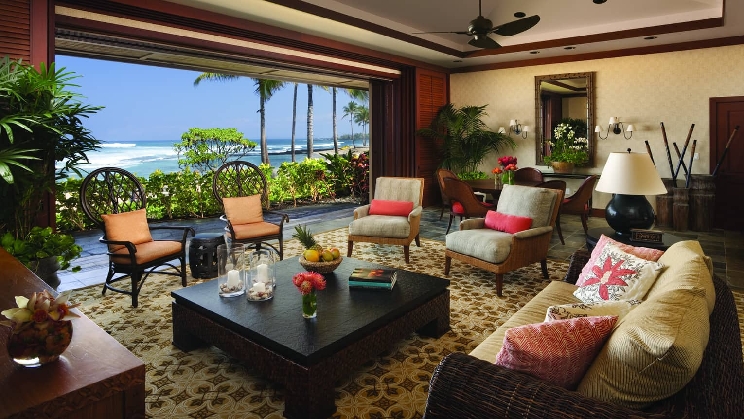 Ho'onanea Villa living room wicker sofa, cushioned chairs by open wall, ocean view