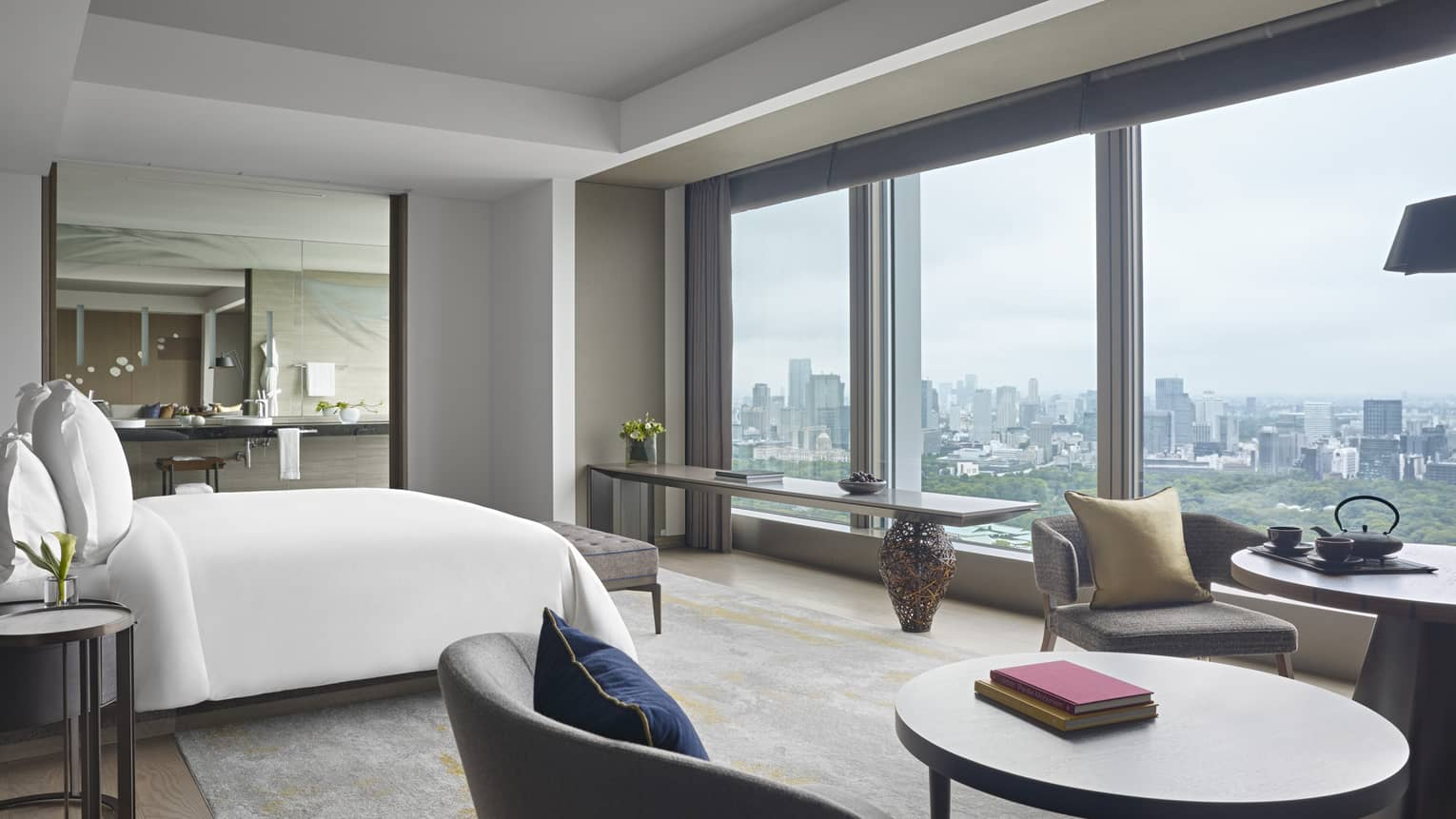 Hotel suite with a king bed, round table and chairs and a wall of windows overlooking Tokyo