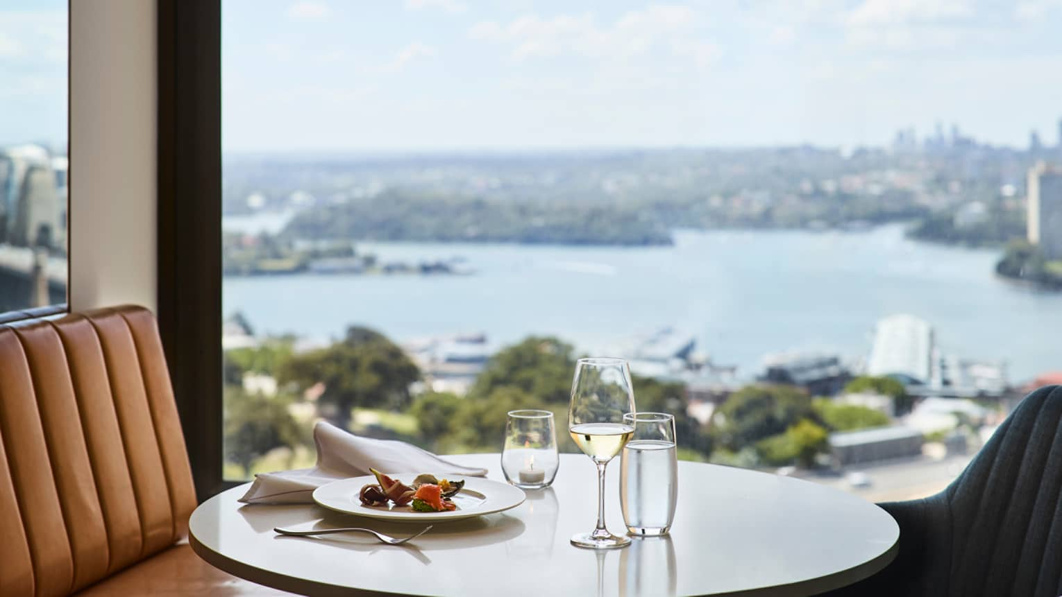 Lounge 32 meal, glass of white wine on round table by window with harbour views