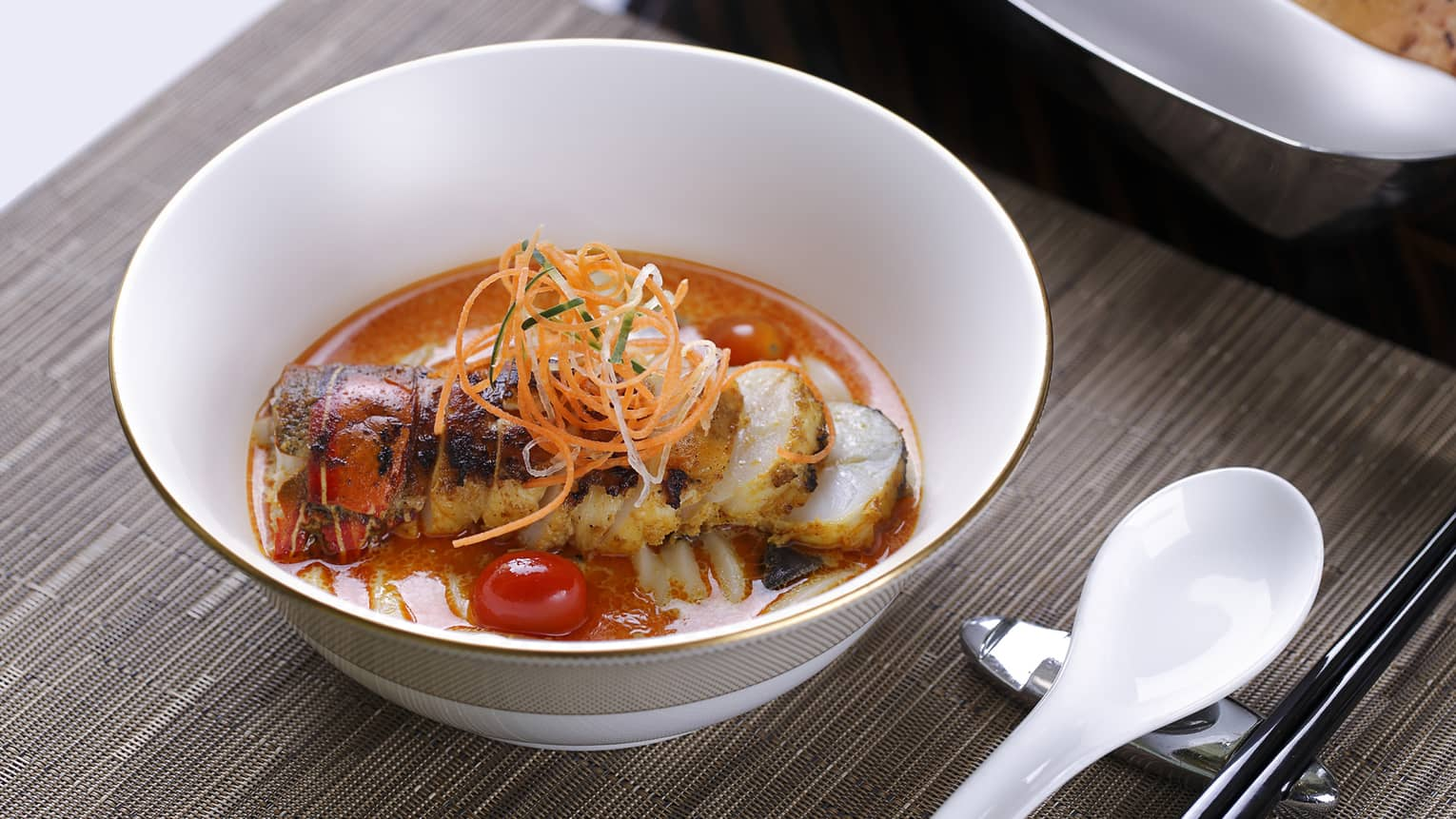 Bowl with lobster in red sauce, carrot garnish
