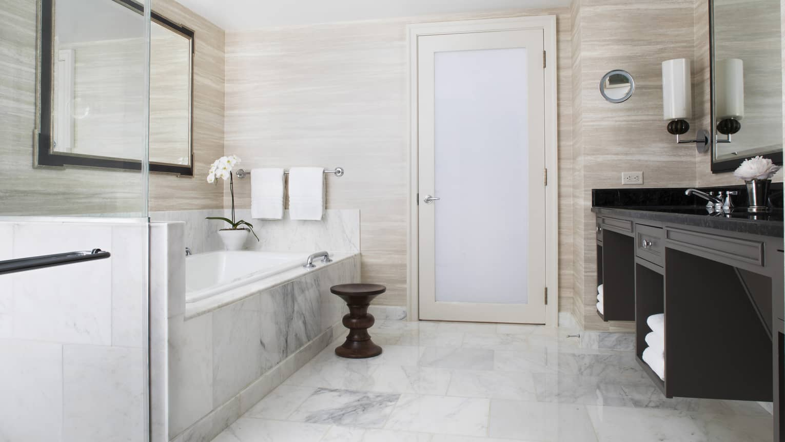 A light colored bathroom with a marble bathtub