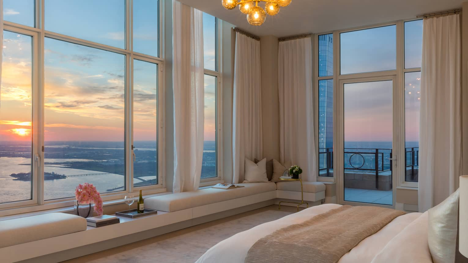 Bed with folded beige blanket across from corner picture windows, sunset views