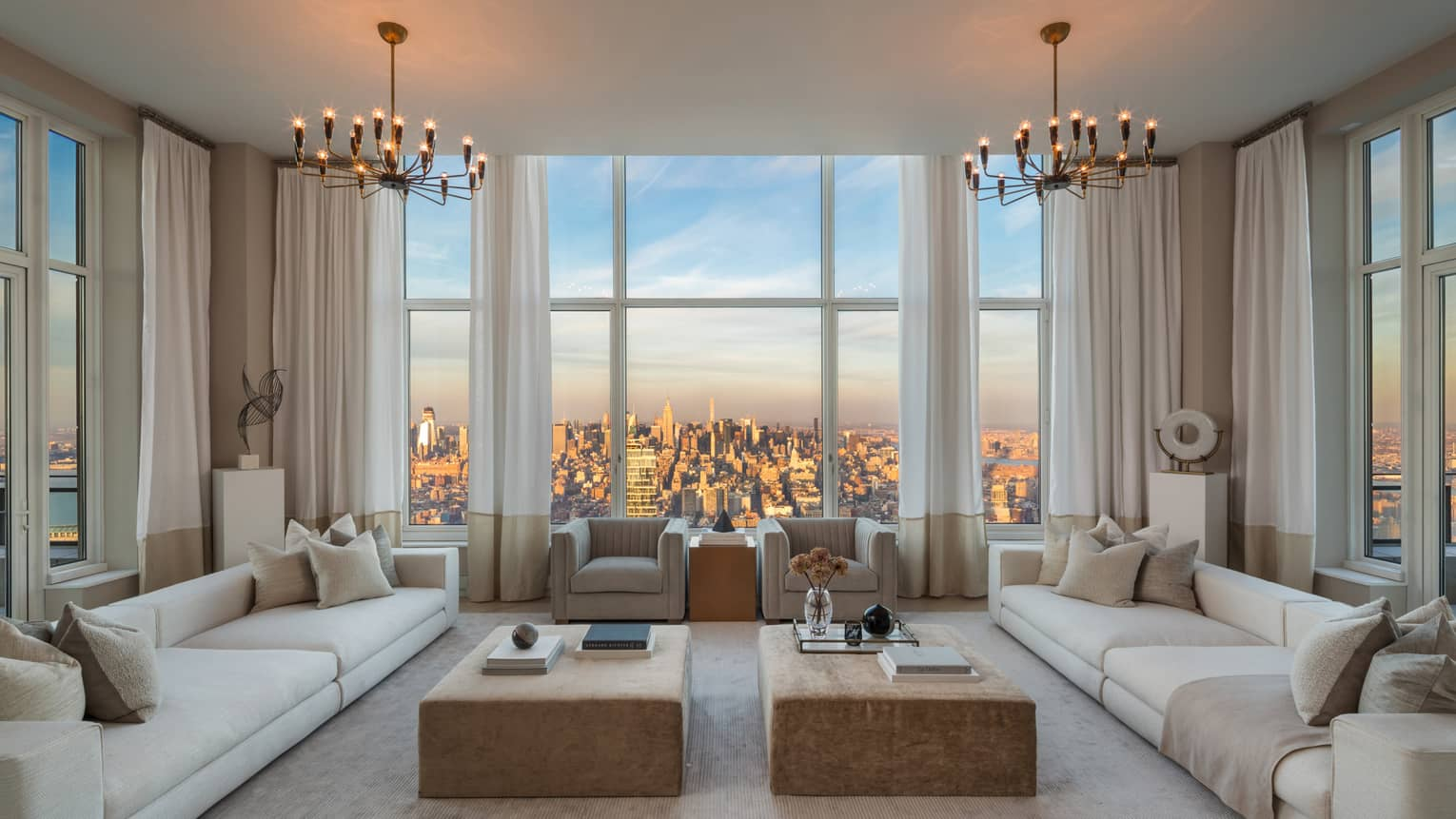 Living room with two long white sofas, armchairs around coffee tables, picture windows with city views