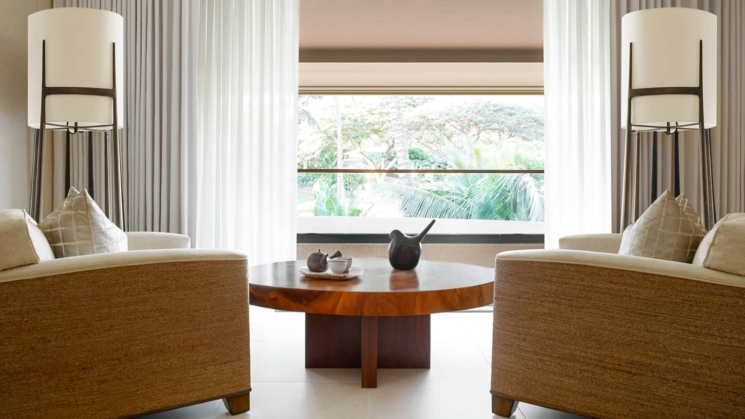 Large armchairs around wood table, sunny window in Couples Suite
