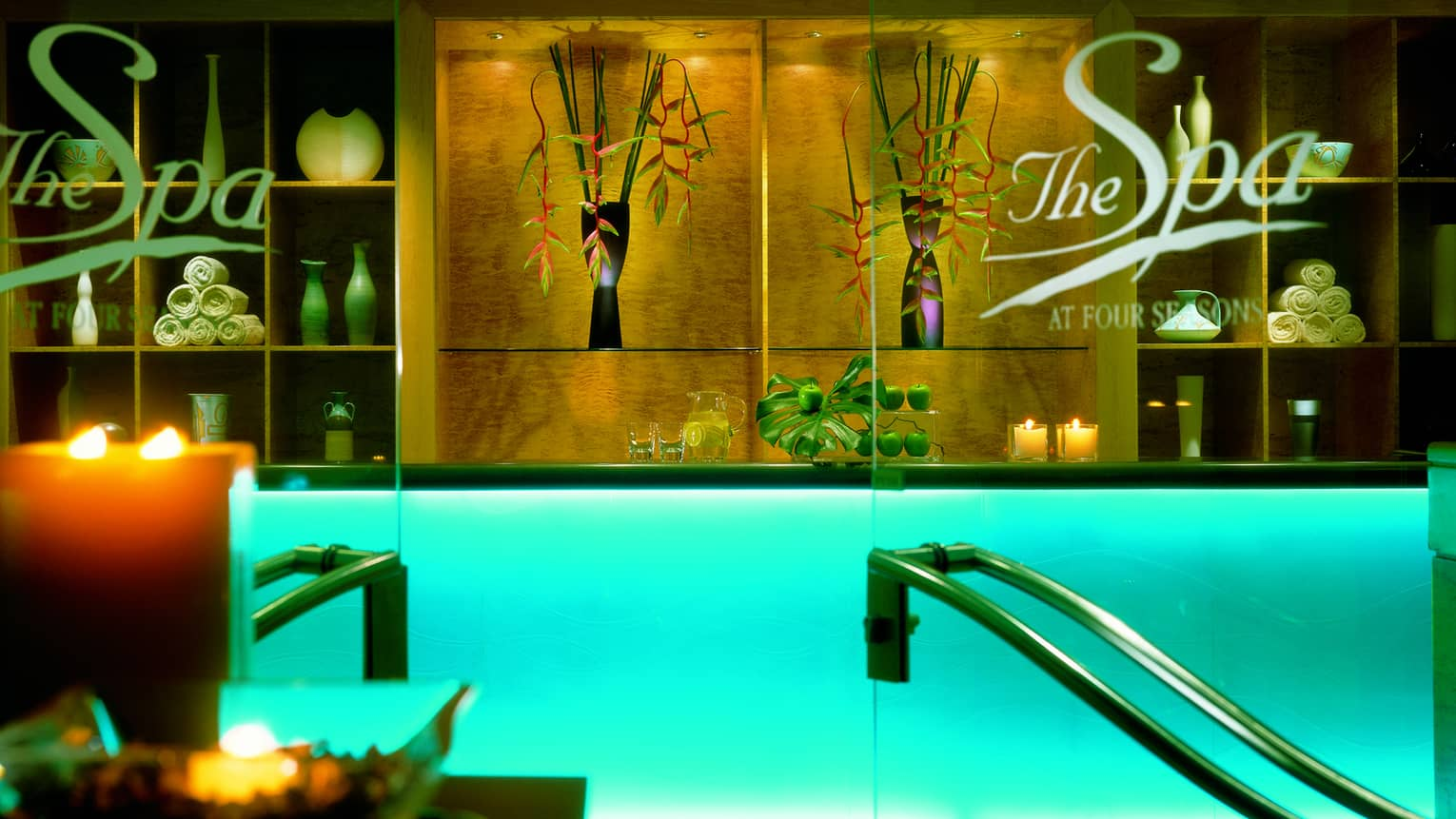 Glass doors at spa lobby, reception desk with with glowing candles, rolled up white towels on shelf