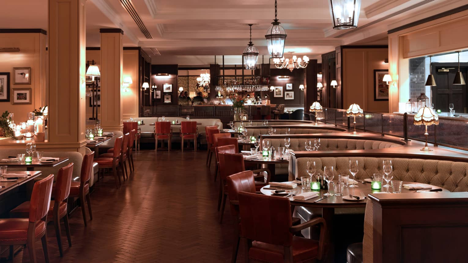 Restaurant with dark wood floors, row of tables with curved booths and red leather chairs, hanging chandeliers