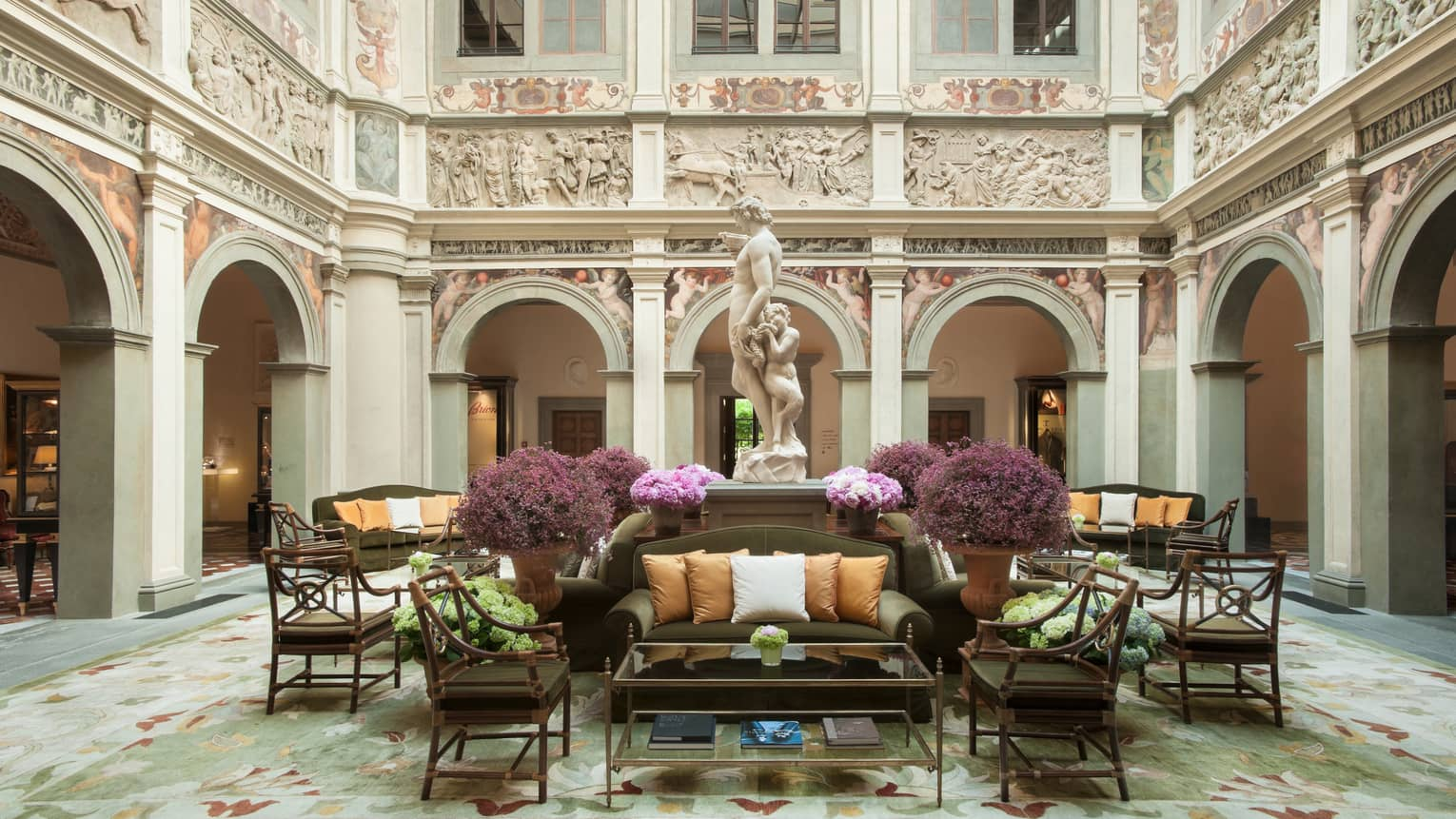 Hotel lobby sofas, chairs under statue, high ceilings and ornate walls