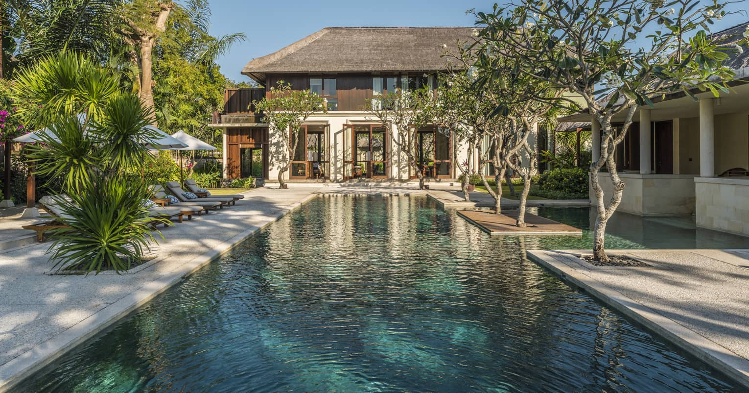 Two-storey villa at end of long outdoor swimming pool lined with trees, tropical plants