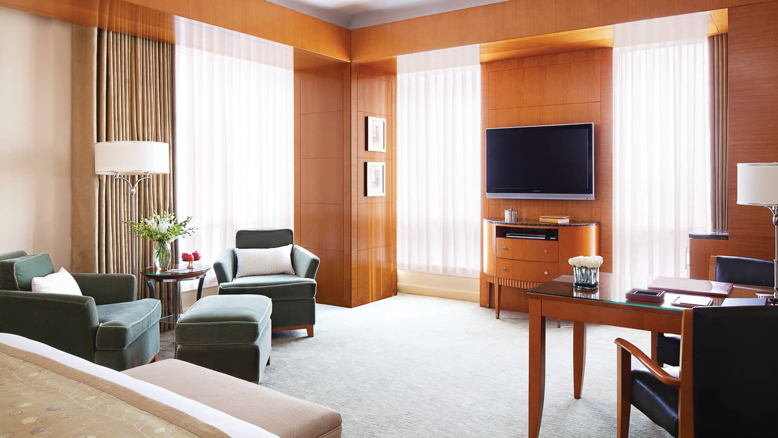 Executive Premier Room wood panel walls, sunny windows with sheer curtains, bed, TV, chairs