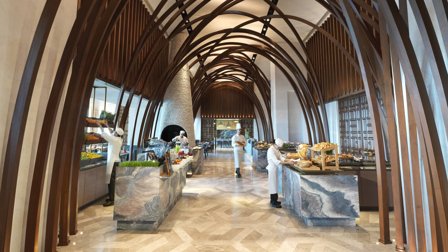 Soaring ceilings, wood arches over marble buffet tables where chefs prepare food
