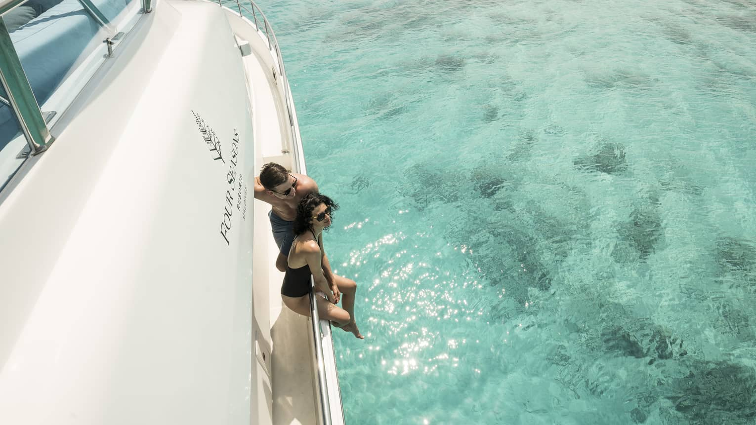 A couple lounges on the side of a yacht in a blue lagoon