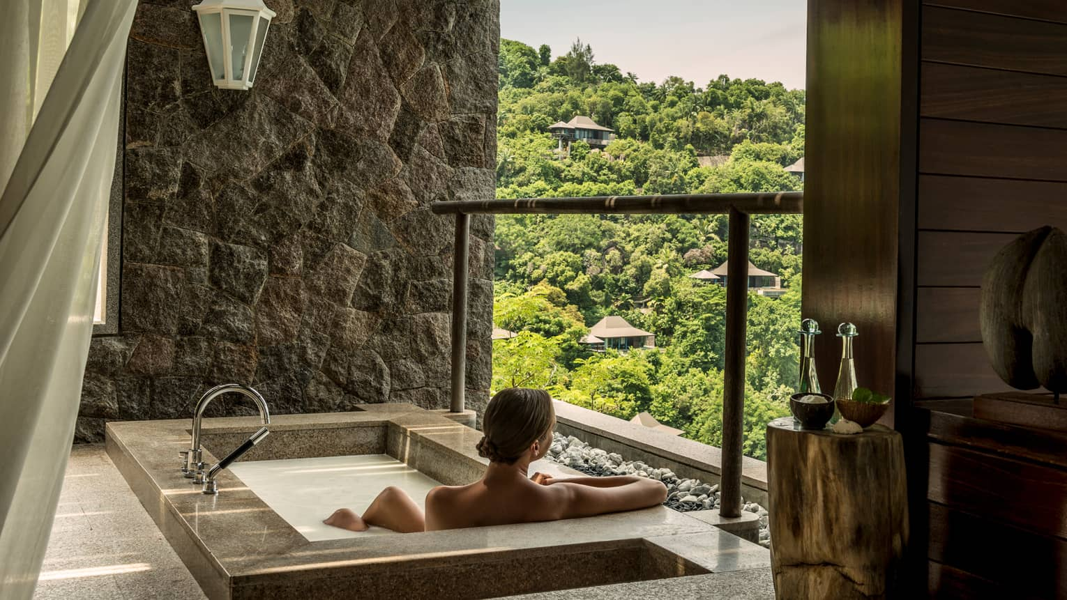 Back of woman sitting in rectangular hot tub, looking out open wall at mountain
