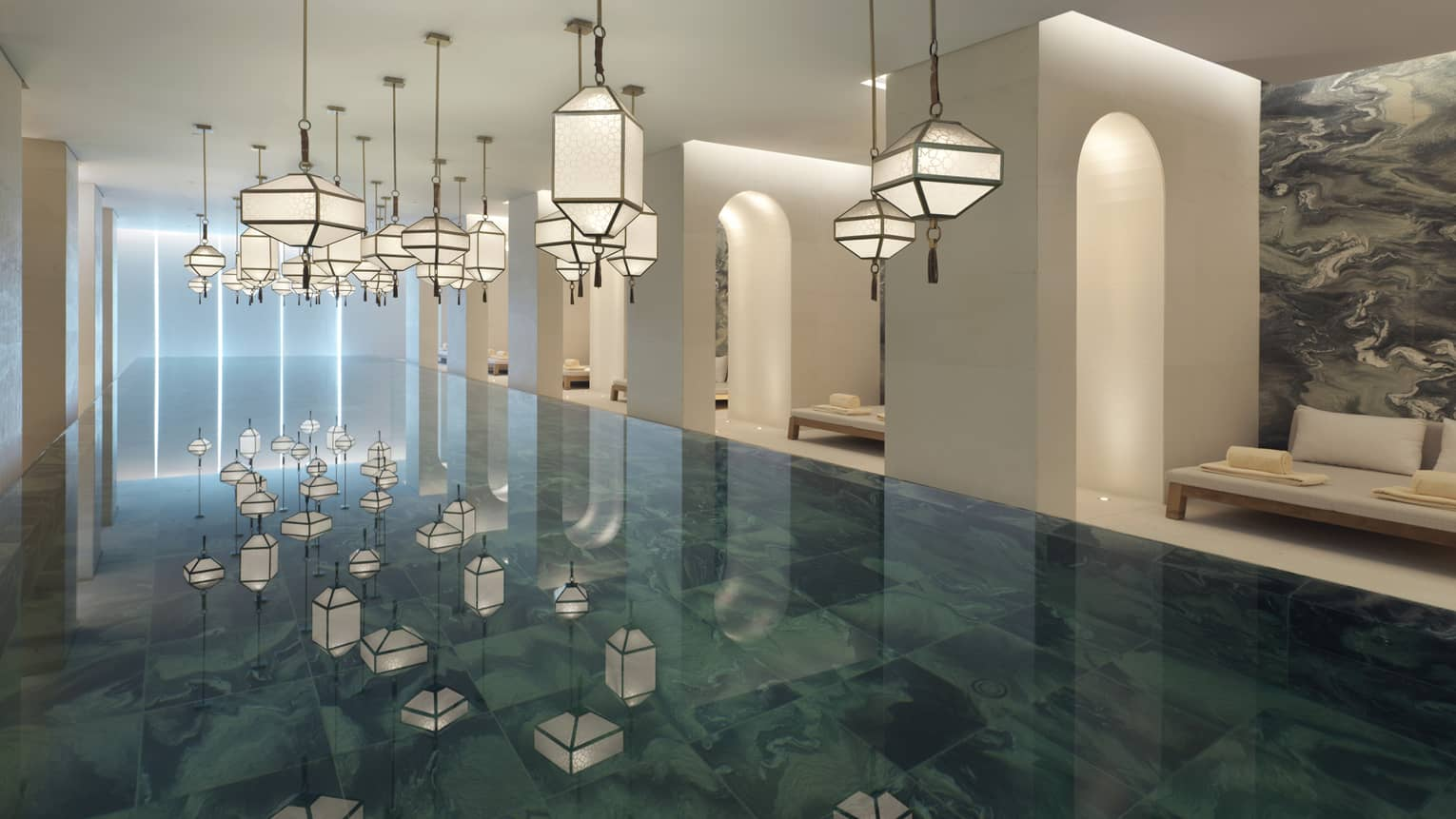 Several modern white lanterns hanging above Indoor Spa Pool, reflected on water