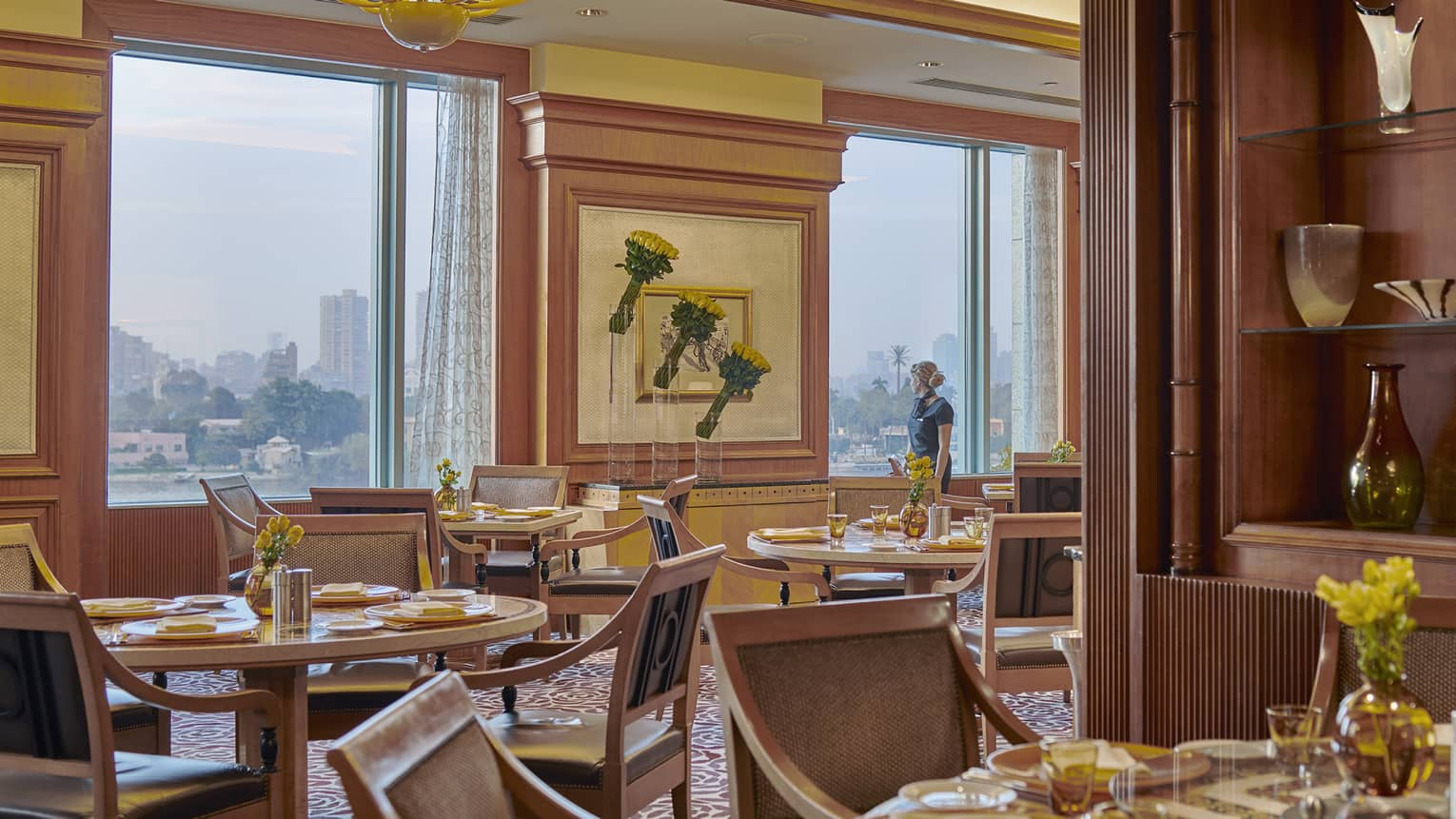 Hotel staff stands at window overlooking river and city in dining room beyond tables, chairs