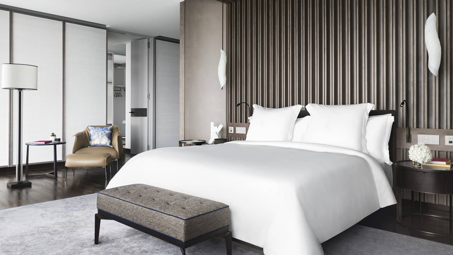 Hotel suite bedroom with white king bed and wooden accent wall/ceiling
